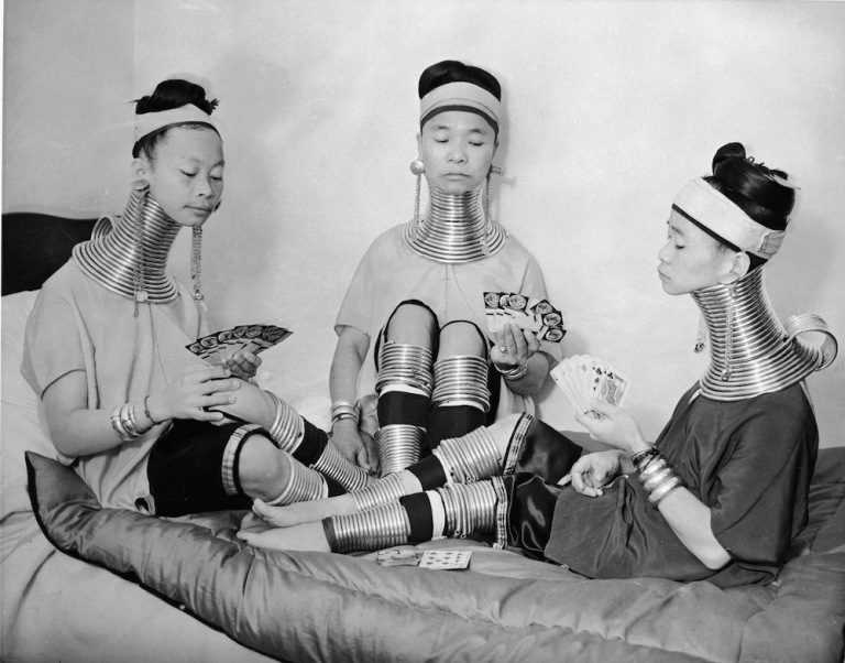 Three Burmese women members of a circus play cards as they wear the brass neck and leg rings traditionally worn by Padaung women since childhood and which cannot be removed, London, January 4, 1935. (Photo by Keystone/Getty Images)